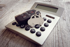 Car shape keyring and key on calculator. Concept for motoring costs, finance, insurance, servicing or fuel bills Royalty Free Stock Photos
