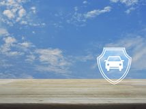Business automobile insurance concept. Car with shield flat icon on wooden table over blue sky with white clouds, Business automobile insurance concept royalty free stock images