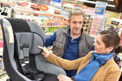 Car shop salesman selling child seat to client. Car shop seller helping customer to choose child seat Stock Photo