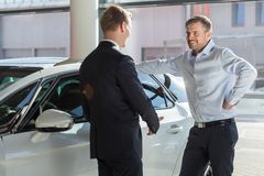 Car showroom client. Image of smiling car showroom client talking with seller Royalty Free Stock Photography