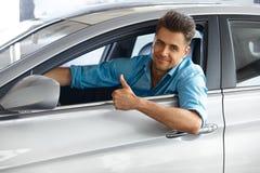 Car Showroom. Happy customer inside Car of His Dream. Stock Photography