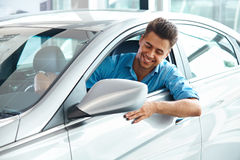 Car Showroom. Happy Man inside Car of His Dream. Stock Photography
