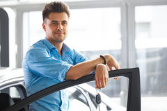 Car Showroom. Happy Man With Keys To The Car Of His Dreams. Royalty Free Stock Image
