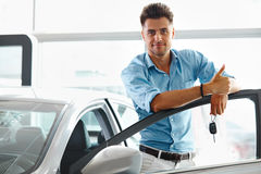 Car Showroom. Happy Man With Keys To The Car Of His Dreams. Stock Photography