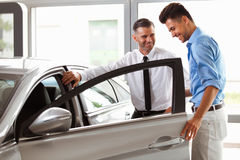 Car Showroom. Vehicle Dealer Showing Young Man New Car Stock Photo
