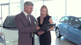 Car showroom, vehicle dealer talking with customer woman. stock video footage