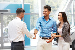 Car Showroom. Young Couple is Meeting with Seller in Auto Salon Stock Photo