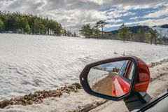 Car side mirror on dirty mountain mud road with snow stock photography