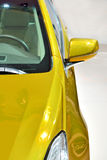 Car side and mirror. Part of a car in yellow color, rear view mirror and car body Royalty Free Stock Photography
