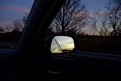 Car Side Mirror Reflection in the Evening. Beautiful blue and yellow sunset reflection during a November evening on a car mirror Stock Photos