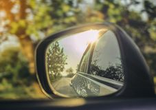 Car side mirrors with natural road travel in warm sunlight.  royalty free stock image