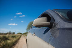 Car side view in dust and blured summer field on ground road Royalty Free Stock Images