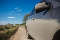 Car side view in dust and blured summer field on ground road Royalty Free Stock Photos