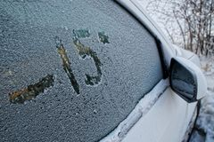 Car side window in hoarfrost. Figure on the glass. stock photos