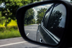 Car side window reflex on the road. Stock Photos