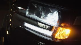 Car with sidelight and headlight blink close in dark. Close-up shot stock video footage