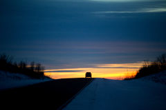 Car silhouetted on a hilltop. One small travelling car silhouetted on a hilltop of a highway at sunset in a winter landscape Stock Photography