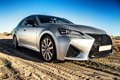A japan car Lexus gs in silver color without logos in the desert in golden hour. A car in silver color without logos in the desert in golden .hour royalty free stock photos