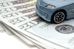 Car sitting on currency: new car loan. A toy car sitting on currency: new car loan royalty free stock images