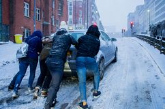 Car slipping in heavy snow in Birmingham, United Kingdom. Birmingham, United Kingdom - March 02 2018 : Unidentified people pushing a car which is slipping during royalty free stock photos
