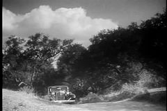 Car slowly navigating hilly country road, 1930s stock footage