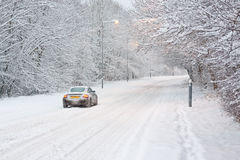 Car in Snow. Single car driving along a deserted snow covered road surrounded by trees stock photos