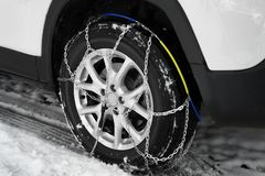 Car with snow chain on tire. Winter season. Car with snow chain on tire, closeup. Winter season royalty free stock images