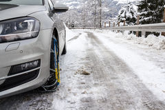 Car with snow chains on iced street. In Alps stock images