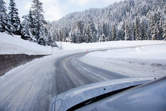 Car on a snow covered road. A car drives on a snowy street towards a curve in a winter landscape Royalty Free Stock Photo