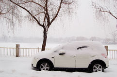 Car in snow beside lake. A white car parked at the bank of lake under snow royalty free stock photography
