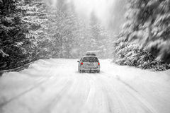 Car in snow storm. Car driving during winter snow taken through a windshield covered with blured snowflakes stock image