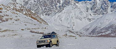 Car among snow tops. The car going on the snow plain against the background of snow-covered mountains and a glacier Stock Images