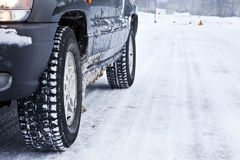Car on a snowy forest road. Close up of a cars tires on a snowy road Stock Photo