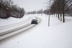 Car in snowy road. Back view of a car on a street full of snow Stock Photos