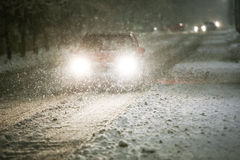 Car on snowy road. A car driving on the road in the aggravated traffic due to strong snowfall Stock Photos