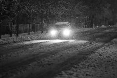 Car in snowy traffic black and white. A car driving on the road in the aggravated traffic due to strong snowfall Royalty Free Stock Photography
