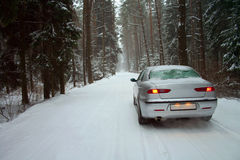 Car in a snowy winter forest. Car drives in the snowy woods Stock Images