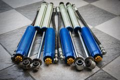 Car spare parts. Used shock absorber with sub tank can adjustable softness for the car was laid out on the tiled floor royalty free stock photos