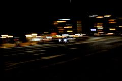 Car speading freeway blurred motion. At the background building citylights in the night Royalty Free Stock Image