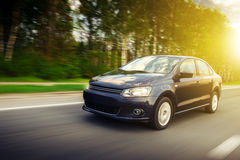 Fast drive car speed on the road at summertime sunset volkswagen polo sedan Royalty Free Stock Photos