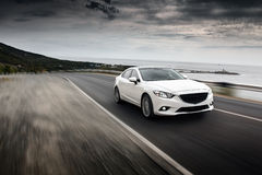 Car speed fast drive on the road near sea at summertime cloudy sky Stock Photos