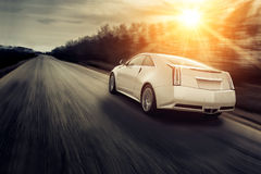 Fast drive car speed on the road cadillac at sunset  Royalty Free Stock Photo