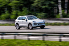 Luxury white Porsche Cayenne speeding on empty highway. Speed car on the road Royalty Free Stock Image