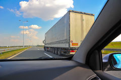 Car speeding over a truck on a highway Royalty Free Stock Image