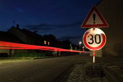 Car speeding through a speed limit zone. Within a small town at nightfall Royalty Free Stock Photography