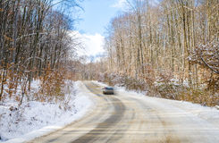 Car speeding through the woods on a winter day Stock Photos