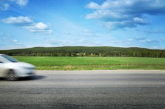 The car speeds along a country road, surrounded by forest and blue sky Royalty Free Stock Image