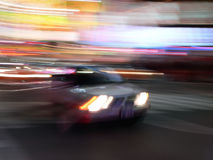 Car speeds through Times Square, New York City. A fast luxury car speeds through the streets in Times Square, New York City stock photography