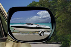 Car & speedy boat on paradise beach. Vacationers arrived to tropical beach. Reflection on the back view mirror of car:  the speedy boat on track is pushing Royalty Free Stock Image