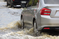 Car splashes through a large puddle on a flooded. Street Royalty Free Stock Photography